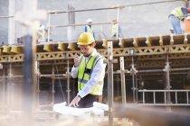 Ingénieur examinant les plans sur le chantier de construction — Photo de stock