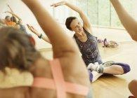 Lächelnde Fitness-Instruktor führt Übung Strecken Arme — Stockfoto