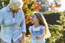 Grandmother and granddaughter holding hands and walking in sunny garden — Stock Photo