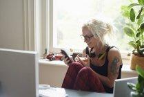 Молодая женщина в наушниках и с татуировками в домашнем офисе — стоковое фото