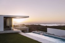 Modern house overlooking ocean at sunset — Stock Photo