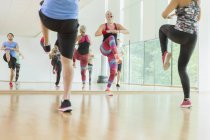 Fitness instructor leading aerobics class — Stockfoto
