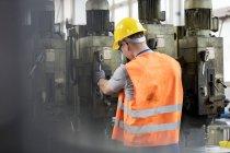 Trabalhador em workwear protetor operar maquinário na fábrica — Fotografia de Stock