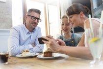 Familie mit Handy Essen Dessert am Café-Tisch — Stockfoto