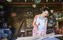 Frau hämmert in Werkstatt Holzbretter — Stockfoto