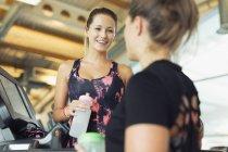 Усміхаючись жінок говорити і питної води в тренажерний зал — стокове фото