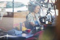 Lächelnde Frau mit Kopfhörer am Laptop im café — Stockfoto