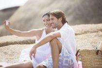 Paar macht gemeinsame Fotos am Sandstrand — Stockfoto