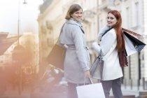 Портрет улыбающихся женщин с сумками на городском тротуаре — стоковое фото