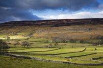Nuvens sobre colinas rurais durante o dia — Fotografia de Stock