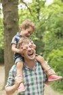 Figlio giocoso che copre occhi di padri in boschi — Foto stock