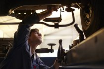 Mechanic working under car in auto repair shop — Stock Photo