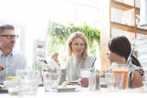Family eating lunch at cafe table — Stockfoto