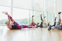Fitness instructor guiding exercise class stretching legs — Stockfoto