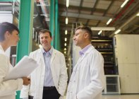 Scientists and businesswoman talking in factory — Stock Photo