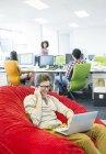Бизнесмен, работающих в погремушка кресло в офис — стоковое фото