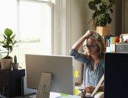 Mulher estressada com a mão no cabelo segurando cartão de crédito no computador no escritório em casa — Fotografia de Stock