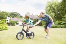 Отец толкает сына на велосипеде на заднем дворе — стоковое фото