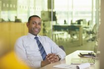 Businessman smiling at desk — Stock Photo