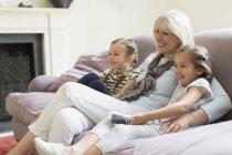 Nonna e nipoti guardando la TV sul divano del soggiorno — Foto stock