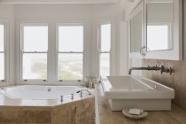 Sink and jacuzzi tub in luxury master bathroom — Stock Photo