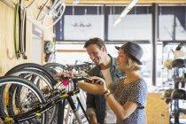Casal olhando para etiquetas de preço em bicicletas na loja de bicicletas — Fotografia de Stock