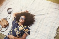 Overhead view smiling woman with afro laying on blanket outdoors — Stock Photo
