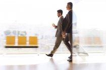 Uomini d'affari che cammina in corridoio aeroporto — Foto stock