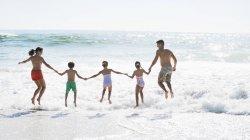 Семья, прыжки в серфинга на пляже — стоковое фото