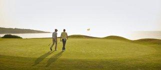 Caucasian men walking on golf course — Stock Photo
