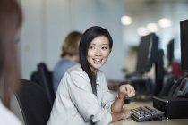 Улыбающаяся деловая женщина разговаривает с коллегой в офисе — стоковое фото