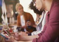 Человек с цифровым планшетом и сотовым телефоном в кафе — стоковое фото
