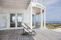 Cadeira de plataforma no convés com vista para a praia — Fotografia de Stock