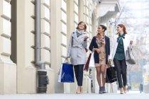 Donne con borse della spesa ne e camminare sui marciapiedi della città — Foto stock