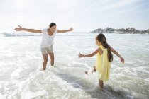 Мать и дочь, играя в серфинга на пляже — стоковое фото