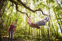 Father pushing daughter on rope swing in forest — Stock Photo