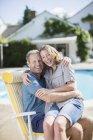 Пара сидящих в шезлонге у бассейна — стоковое фото