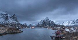 Snow covered mountain range above fishing village at dusk, Reine, Lofoten Islands, Norway — Stock Photo