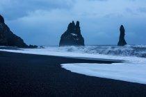Formaciones rocosas y el océano tormentoso en el anochecer Reynisdrangar, Vik, Islandia - foto de stock