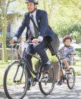 Бизнесмен в костюм и шлем велосипеде тандеме с сыном — стоковое фото