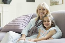 Portrait smiling grandmother and granddaughter on living room sofa — Stock Photo