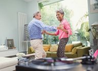 Playful mature couple dancing in living room — Stockfoto