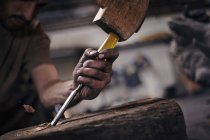 Close up of blacksmith chiseling wood with tool — Stock Photo