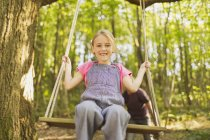 Portrait smiling girl swinging on rope swing in forest — Stock Photo