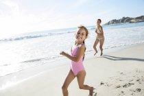 Mother and daughter running on beach — Stock Photo