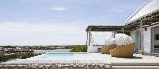Бассейн, стулья и патио современного дома — стоковое фото