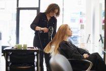 Parrucchiere asciugatura clienti capelli lunghi in salone — Foto stock
