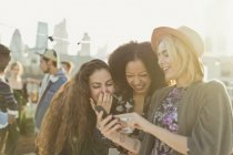 Young women laughing and texting with cell phone at rooftop party — Stockfoto