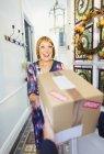 Reife Frau empfangende Paketlieferung an Haustür lächelnd — Stockfoto