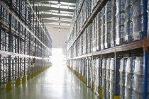 Піддони пляшки з водою на полицях склад — стокове фото